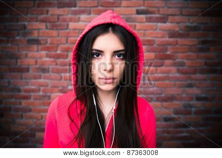 Beautiful young woman with headphones over brick wall. Looking at camera. Wearing in pink hood