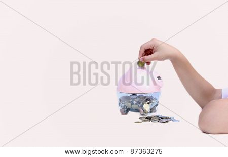 Child Putting Coin Into Big Piggy Bank