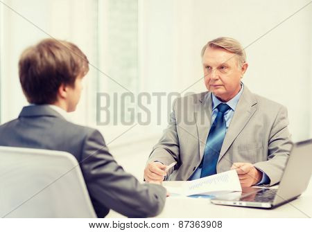 business, technology and office concept - older man and young man having meeting in office