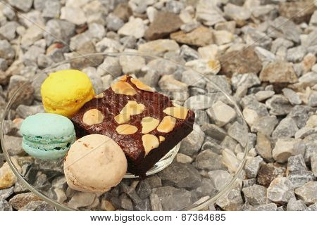 Brownies With Macaron In A Dish On The Background Of Rocks.