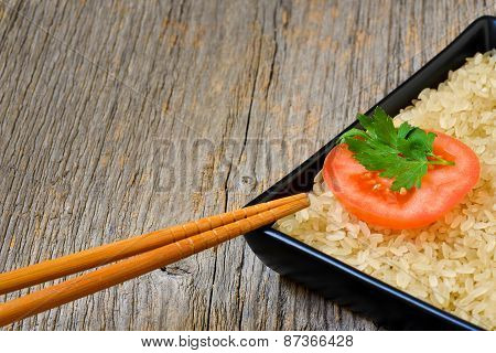 Plate With Uncooked Rice And Tomato Slice