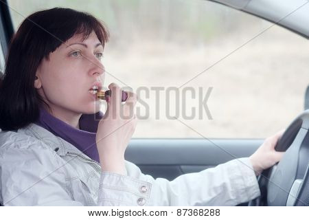 Women make up lips at the wheel the car