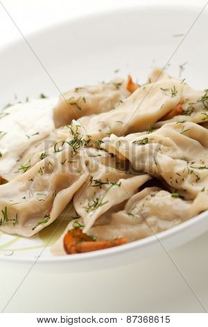 Dumplings with Potato and Mushrooms. Garnished with Dill and Sour Cream Sauce