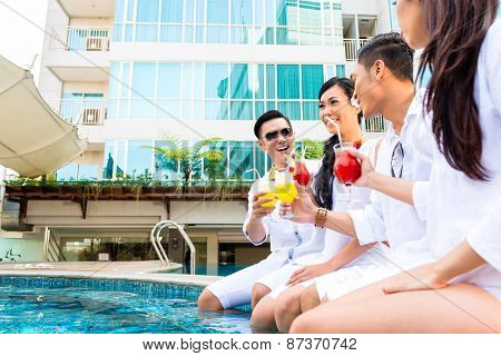 Friends drinking cocktails by swimming pool