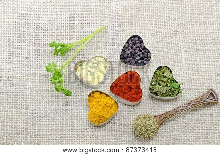 Various Spices In Heart Chaped Containers On A Tablecloth