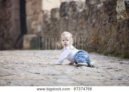 Baby boy crawling on stone paved sidewalk