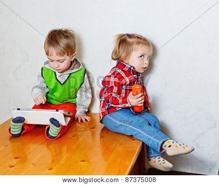 Brother And Sister Sitting On Kitchen Table With Tablet Pc And Phone