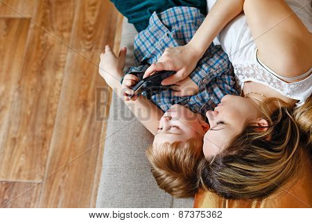 Mom And Son Lying On The Couch With A Tablet Pc