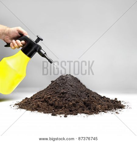 Watering A Pile Of Soil