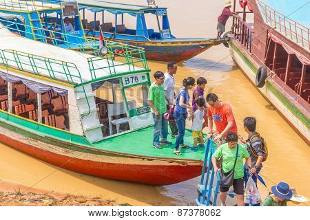 Kampong, Siem Reap, Cambodia February,27 2015: Undefined tourists going to a floating village on the Tonle Sap lake where people live on the water in the city of Siem Reap, Cambodia, February 27, 2015