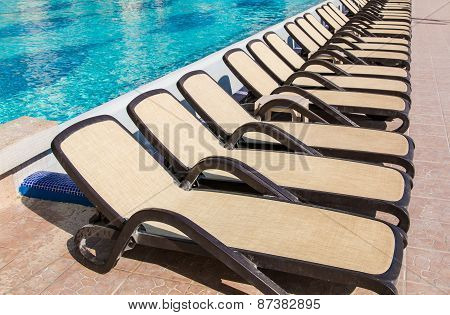 Line Of Empty Chaise-longue Near Swimming Pool