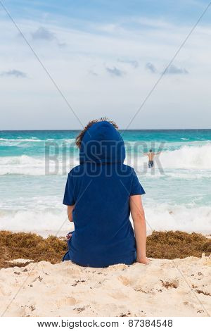 Woman Sitting On The Beach With Sand And Seaweeds, Looking At The Stormy Ocean