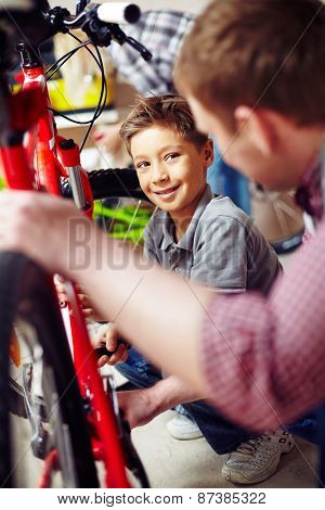 Cute boy learning to repair bike in garage