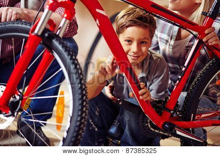 Little boy with bicycle looking at camera
