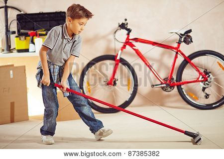 Adolescent boy with mop cleaning floor in garage