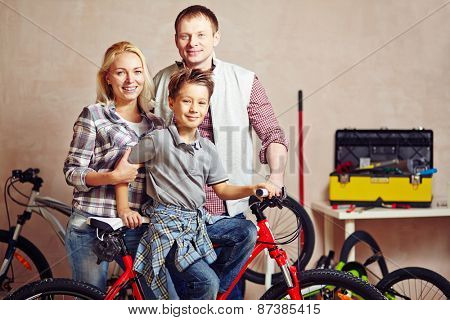 Happy young couple and their son looking at camera in garage