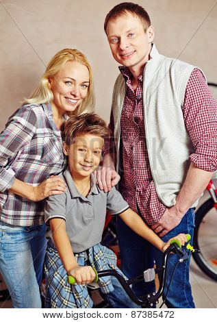 Happy couple and little boy on bicycle looking at camera