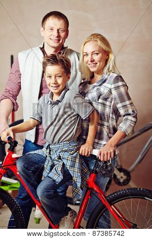 Happy young couple and little boy with bicycle