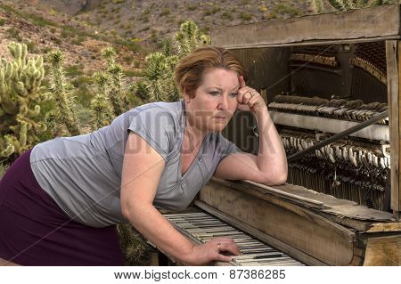 Woman Playing Wooden Piano In Desert With Contemplative Expression