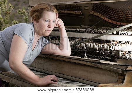 Woman Playing On Piano Looking Into Distance