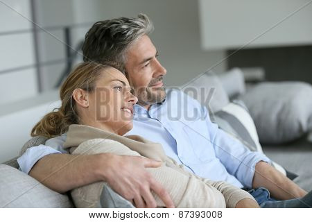 Mature couple sitting in sofa, looking away