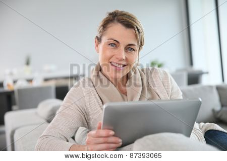 Mature woman sitting in sofa and websurfing with tablet