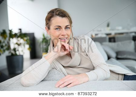 Blond middle-aged woman relaxing in living-room