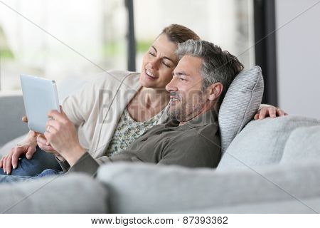 Mature couple using digital tablet relaxing in sofa