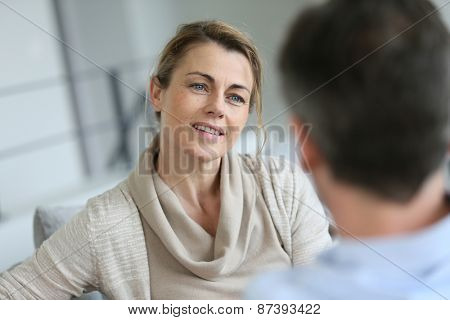 Couple at home sitting in sofa and having a talk