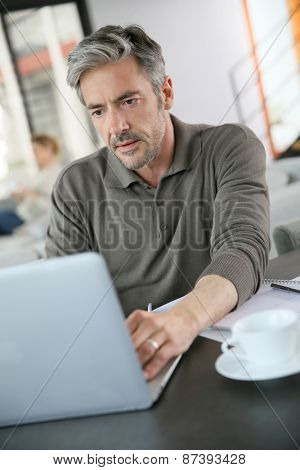 Mature man calculating budget on laptop