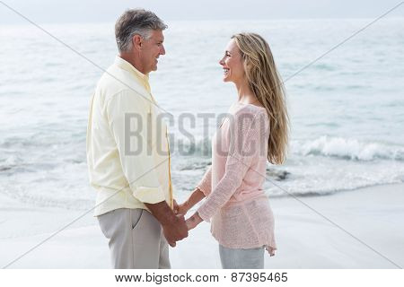 Happy couple holding hands and smiling at each other at the beach