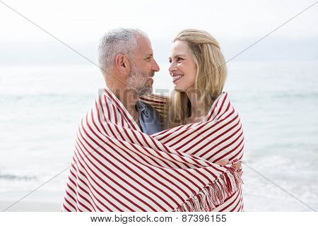 Happy couple smiling at each other with blanket around them at the beach