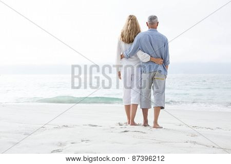 Happy couple hugging each other and looking at the sea at the beach