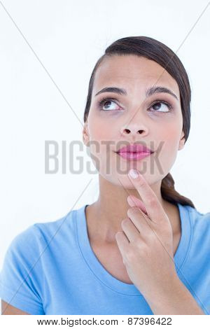 Thoughtful woman looking up with finger on chin on white background