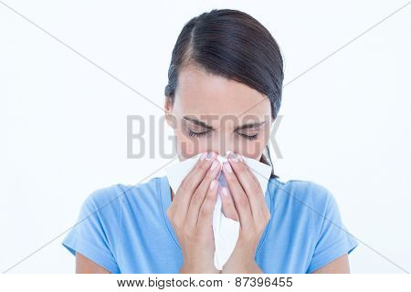 Sick woman blowing her nose on white background