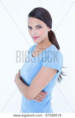 Outraged brunette woman with arms crossed on white background