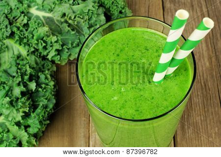 Green kale smoothie close up on wood background