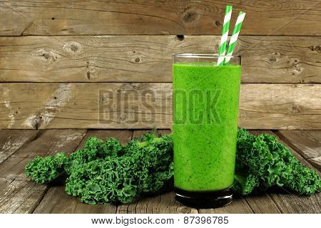 Green smoothie with kale on wood background