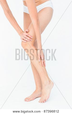 Attractive woman touching her leg on white background