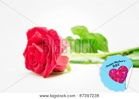 Red rose with stalk and leaves lying on surface against happy mothers day