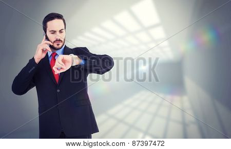 Serious businessman checking the time while on the phone against room with windows at ceiling