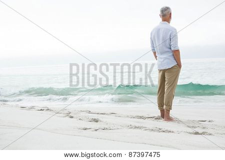 Thoughtful man standing by the sea at the beach