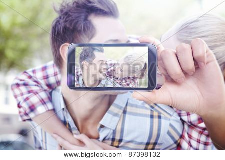 Hand holding smartphone showing against man giving his pretty blonde girlfriend a piggy back