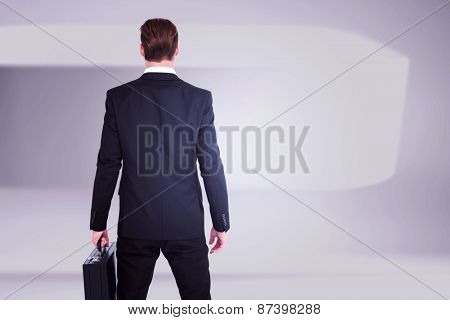 Rear view businessman standing with his briefcase against white abstract room