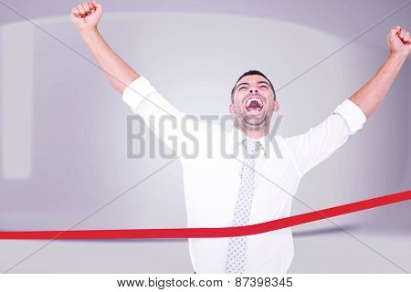 Businessman crossing the finish line against white abstract room