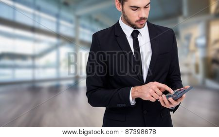Concentrated businessman in suit using calculator against fitness studio