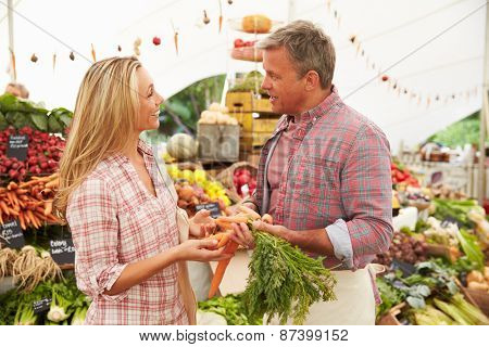 Woman Buying Fresh Vegetables At Farmers Market Stall