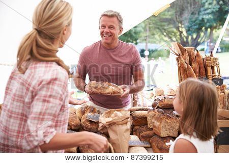 Family Buying Bread From Bakery Stall At Farmers Market