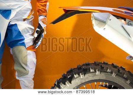 Closeup Image Of A Motocross Biker Protective Clothing And Motocross Bike On Orange Background