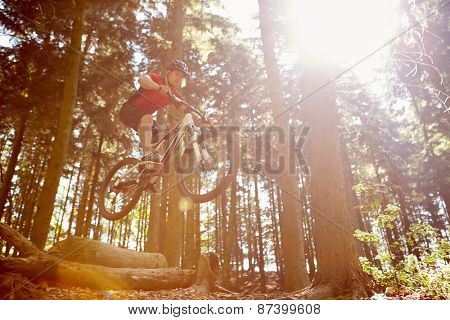 Mid-Air Shot Of Man Riding Mountain Bike Through Woods